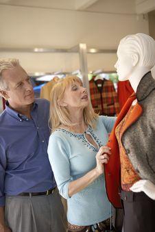 Free Couple Looking At Coat On Mannequin Store Stock Photos - 13585173