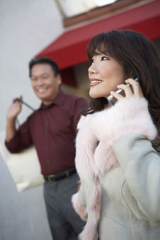 Free Woman Talking On Cell Phone, Husband Holding Bag Stock Images - 13585174