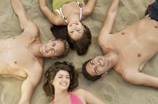 Free Four Young Adults Lying Down In Circle On Sand Stock Photography - 13585202
