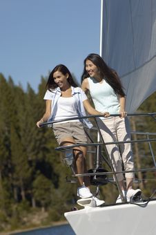 Two Prettyyoung Women Standing On Bow Of Sailboat Royalty Free Stock Photography