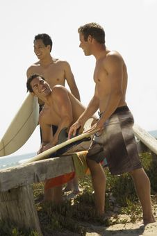 Free Three Surfers Sitting Holding Surfboards Stock Image - 13585291