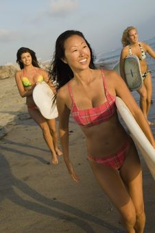 Free Three Female Surfers Carrying Surfboards Stock Photo - 13585310