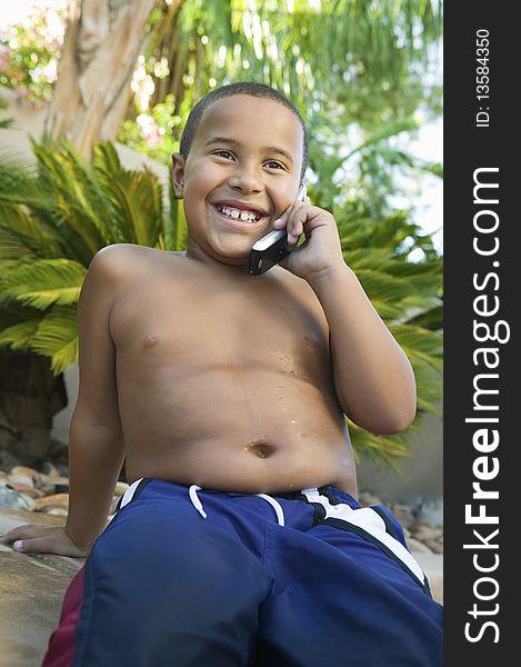 Boy sitting in back yard Using Cell Phone