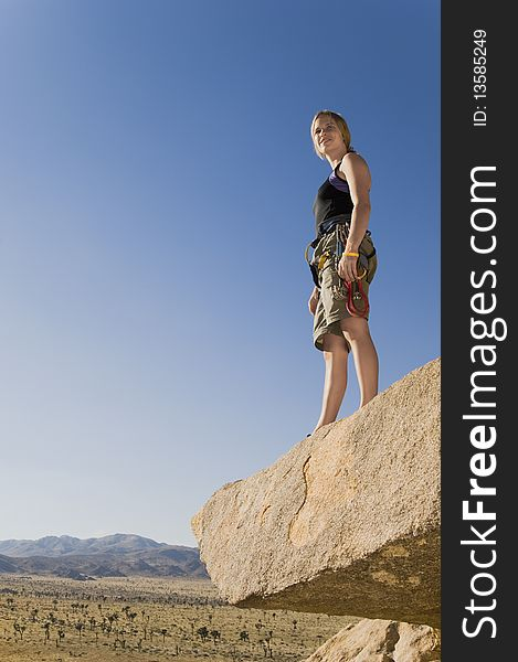Climber standing on Rock Looking at Desert