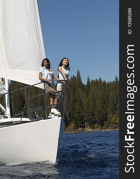 Two young women standing on sailboat