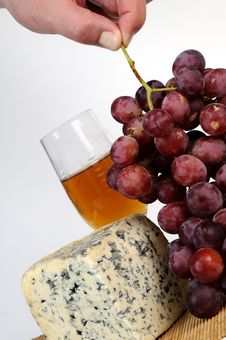 Human Hand Taking Moldy Cheese And Red Grapes Stock Photo