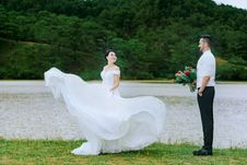 Free Bride Standing In Front Of Groom Holding Bouquet Of Flowers Stock Photos - 135955333