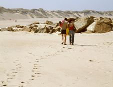 Free Couple Walking Along A Beach Stock Images - 1360374