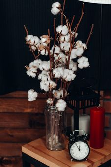 Free White Cotton Flowers In Vase Beside Clock Royalty Free Stock Image - 136045176