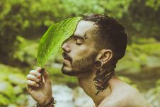 Free Man Holding Green Leaf To His Face Stock Image - 136045341