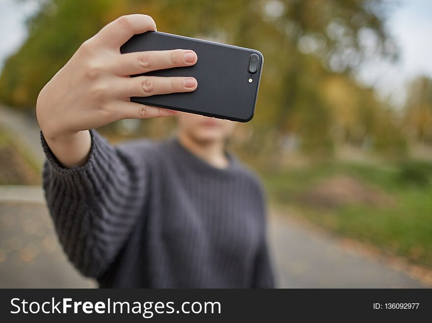 The girl takes a selfie with smartphone