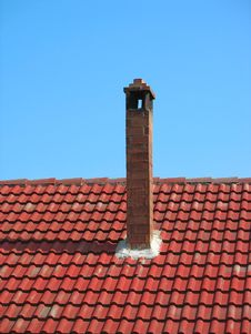 Red Brick Chimney On Tile Roof Over Blue Sky Royalty Free Stock Photography