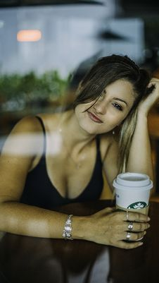 Free Woman Sitting Beside Table Holding Cup Of Starbucks Royalty Free Stock Photos - 136157198
