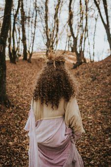 Free Girl In Beige And Purple Long-sleeved Dress Walking Into The Woods Stock Images - 136346354