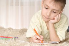 Young Kid With Pencils On The Carpet Stock Images