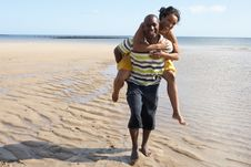 Free Young Man Giving Woman Piggyback Along Shoreline Royalty Free Stock Photography - 13673337