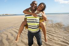 Free Young Man Giving Woman Piggyback Along Shoreline Royalty Free Stock Photography - 13673357