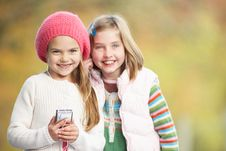 Two Young Girl Outdoors With MP3 Player Royalty Free Stock Photos