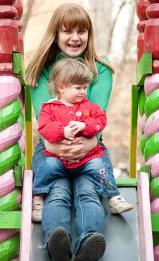 Mother And Daughter Sitting At The Top Of A Slide Royalty Free Stock Images