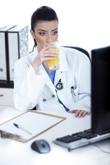 Doctor Drinking A Glass Of Juice At Her Workplace Royalty Free Stock Image