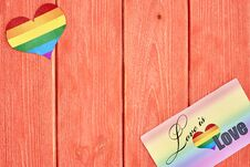 Postcard Love Is Love And A Heart With A Rainbow Of LGBT, On Wooden Texture Background Color Living Coral Royalty Free Stock Photos