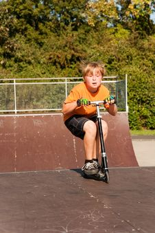 Free Young Boy Jumps With Scooter Over A Ramp At The Sk Royalty Free Stock Photo - 13729265
