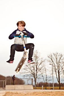 Free Young Boy Jumps With Scooter Over A Ramp At The Sk Royalty Free Stock Photo - 13729345