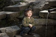 Little Boy Sitting Near Spring Royalty Free Stock Photos