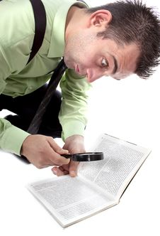Businessman Reading A Book With Magnifying Glass Stock Images