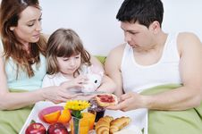 Happy Young Family Eat Breakfast In Bed Stock Image