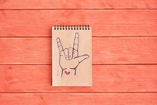 Notebook Of Kraft Paper With A Painted Symbol ASL American Sign Language ILY I Love You That Lies On The Textured Wooden Plank Royalty Free Stock Images