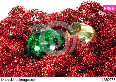 Green and gold ornaments on red garland Stock Photo