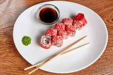 Rolls With Salmon And Cream Cheese And Tomatoes Lie On A White Plate That Has More Wasabi, Pickled Ginger, Soy Sauce And Wooden Stock Images