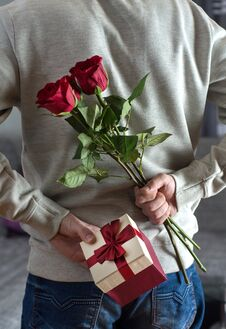 Free Young Man Holding Red Rose Flowers And Gift Box Behind His Back At Home Royalty Free Stock Image - 138218836