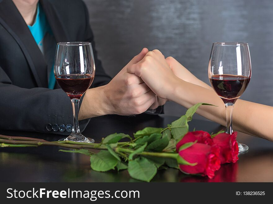 Modern couple hands on restaurant table with two glasses of red wine and roses