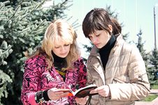Two Girls Read The Book In A Park Royalty Free Stock Photo