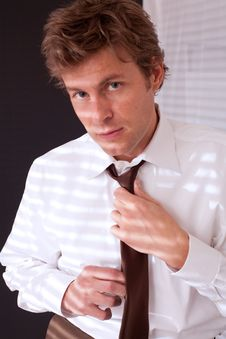 Man Fixing Tie By Window Stock Photos
