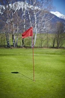 Red Flag Hole Marker At The Golf Course Royalty Free Stock Image