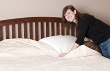 Brunette Woman Makes The Bed Stock Photos