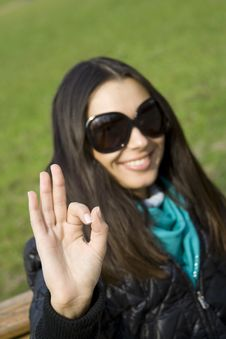 Free Beautiful Girl In A Park Smiling. Hand Sign OK Royalty Free Stock Photo - 13855045