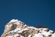 Free Snow-covered High Rocky Cliff Against Clear Blue S Royalty Free Stock Image - 13871356