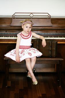 Little Girl Next To A Piano Royalty Free Stock Image