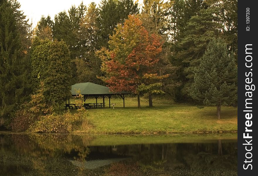 Picnic shelter by pond with fall reflections