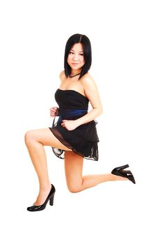Chinese Girl Kneeling In Black Dress. Royalty Free Stock Image