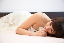 Young Girl Is Lying On A Bed Stock Images