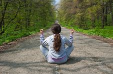 Girl Sitting In The Middle Of The Forest Road Royalty Free Stock Image