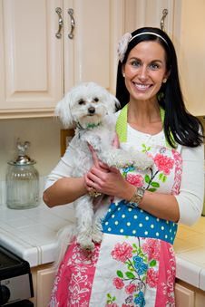 Smiling Woman With Cute Dog In Kitchen Stock Photography