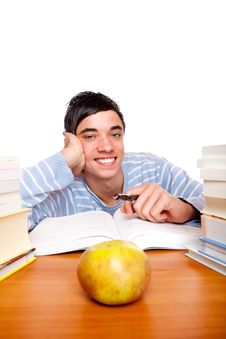 Young Smiling Male Student Learning Between Books Royalty Free Stock Photography