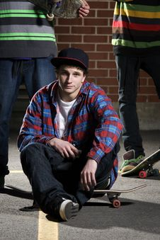Skateboarder Sitting On His Board Stock Photo