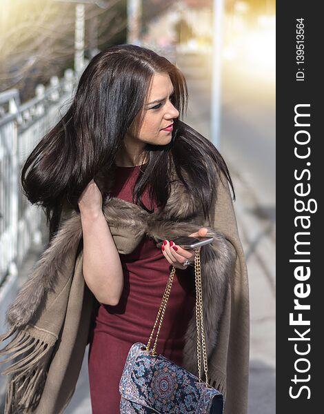 Gorgeous girl in eco fur coat on sidewalk change hair